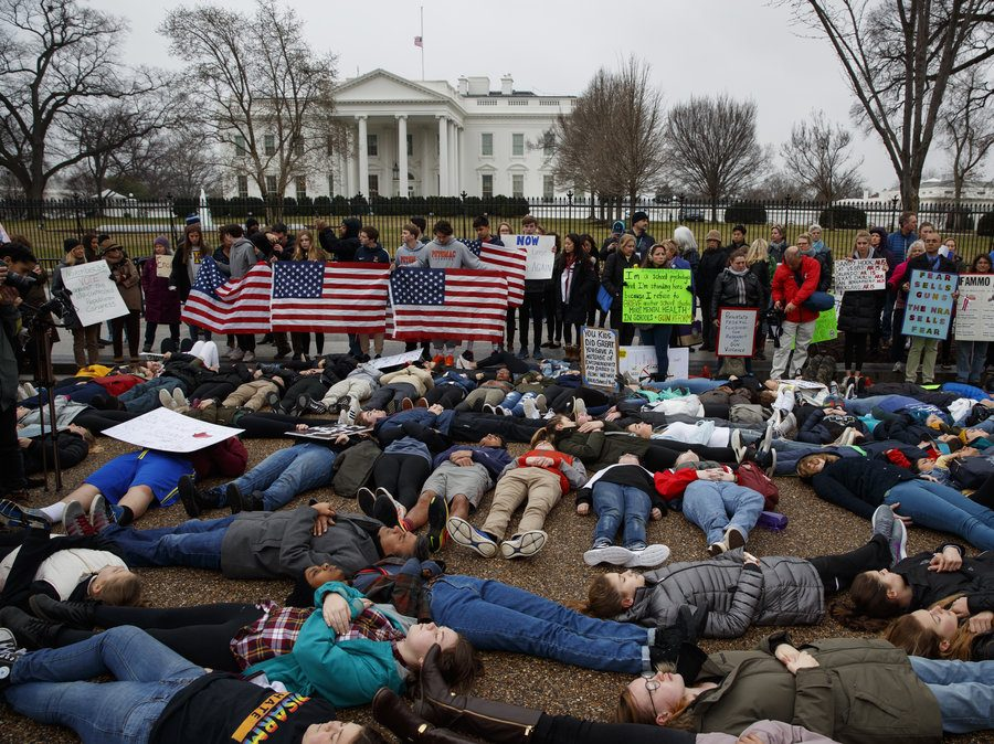 Protesters gathered in front of the White House, some laying down, and some standing with signs.