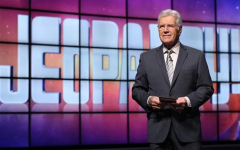 Alex Trebek standing in front of the Jeopardy game board