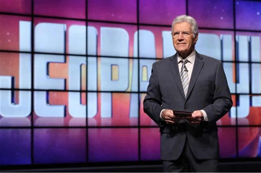 Alex+Trebek+standing+in+front+of+the+Jeopardy+game+board%0A
